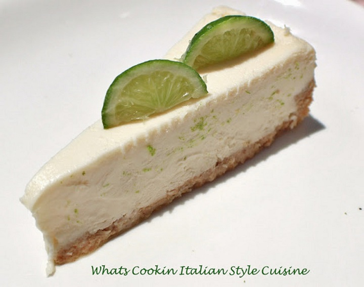 this is a slice of margarita cheesecake on a white plate with slices of lime on top.
