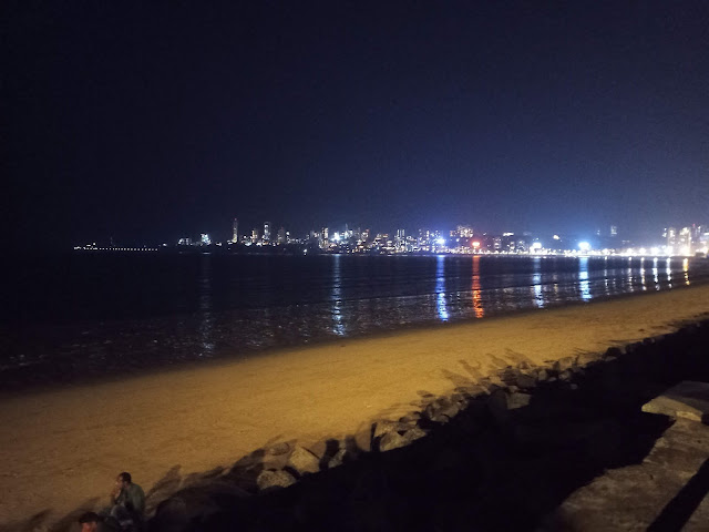 Beach and buildings with lights at night at Queen's Necklace, Marine Drive