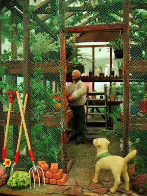 One-twelfth scale miniature green house with a man in a hand-knitted jumper working inside and a dog watching from the doorway.