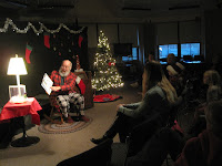 A white bearded man in flannel reads a picture book to an audience of adults and children with a lit Christmas tree to his right and a lamp on a table to his left.