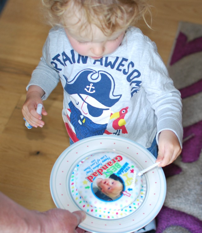toddler placing candles in cake