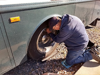 man kneeling and checking air pressure in RV tire