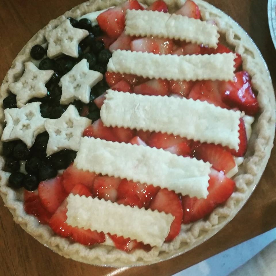 A no bake cheesecake flag pie with just baked strips of pie crusts and stars made seperately for decorating on the 4th of july, memorial day or any patriotic event