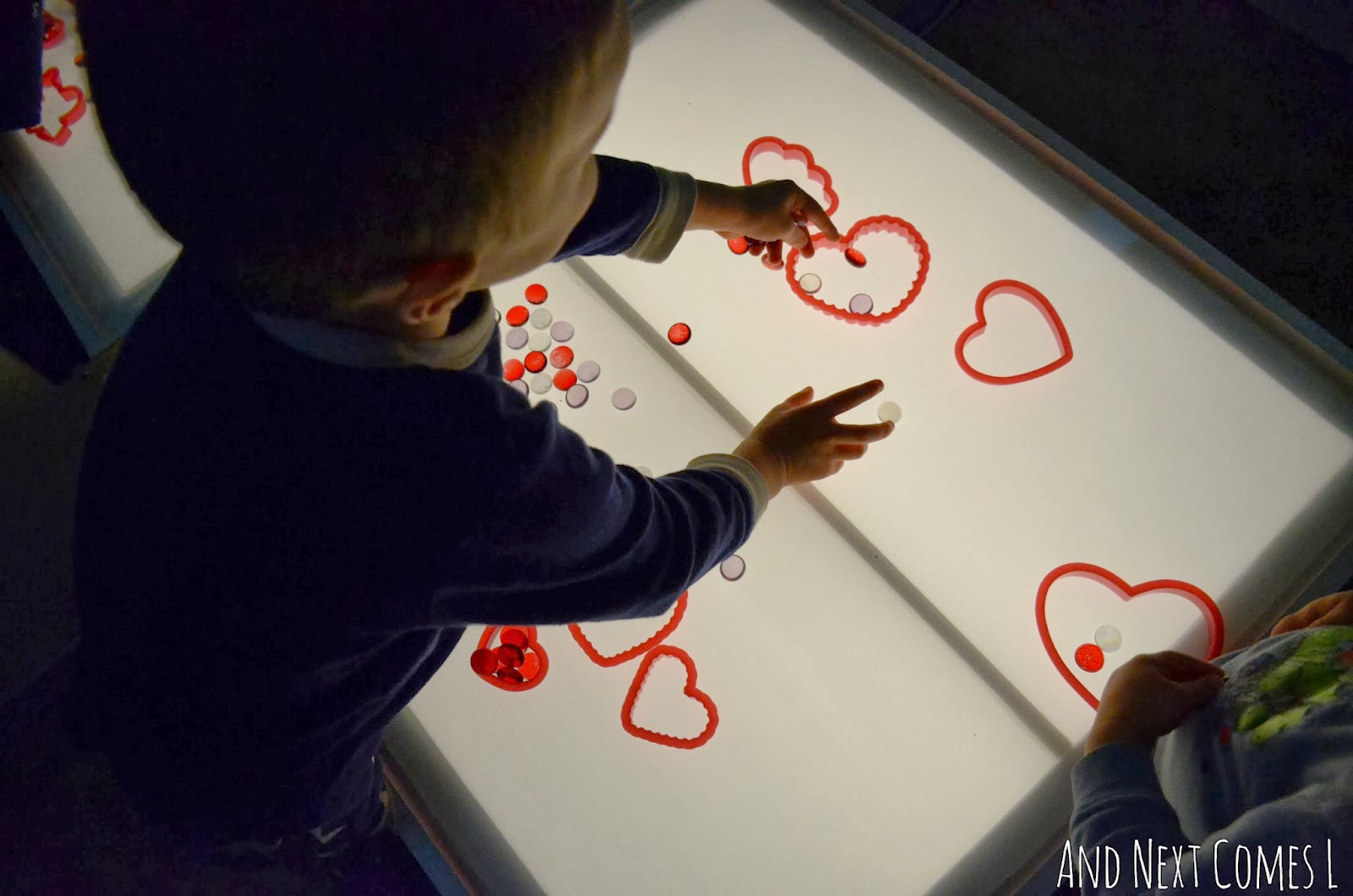 Playing with hearts and glass stones on the light table for Valentine's Day from And Next Comes L