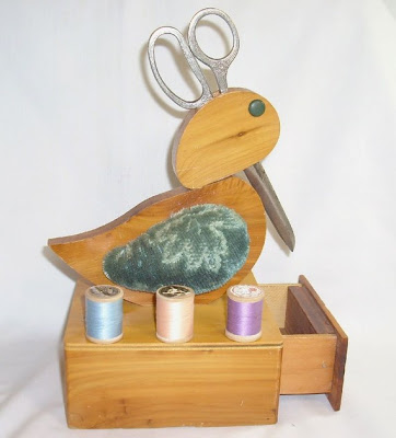 wooden duck that stores scissors - base has a drawer as well as place for spools of thread