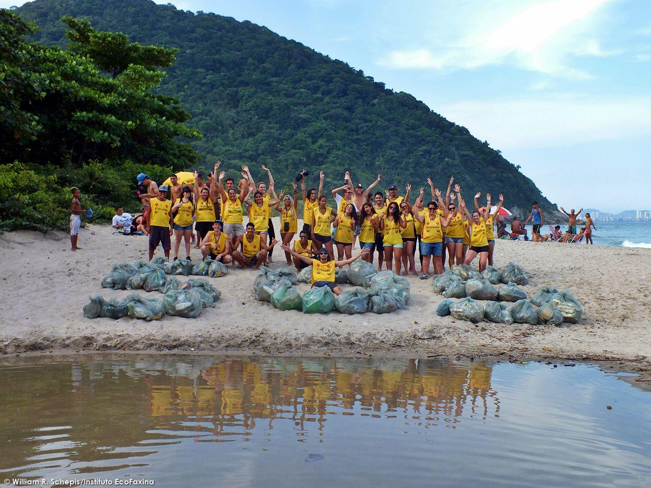 Voluntários posam para foto após coletarem 153 kg de resíduos da praia de Itaquitanduva, em São Vicente