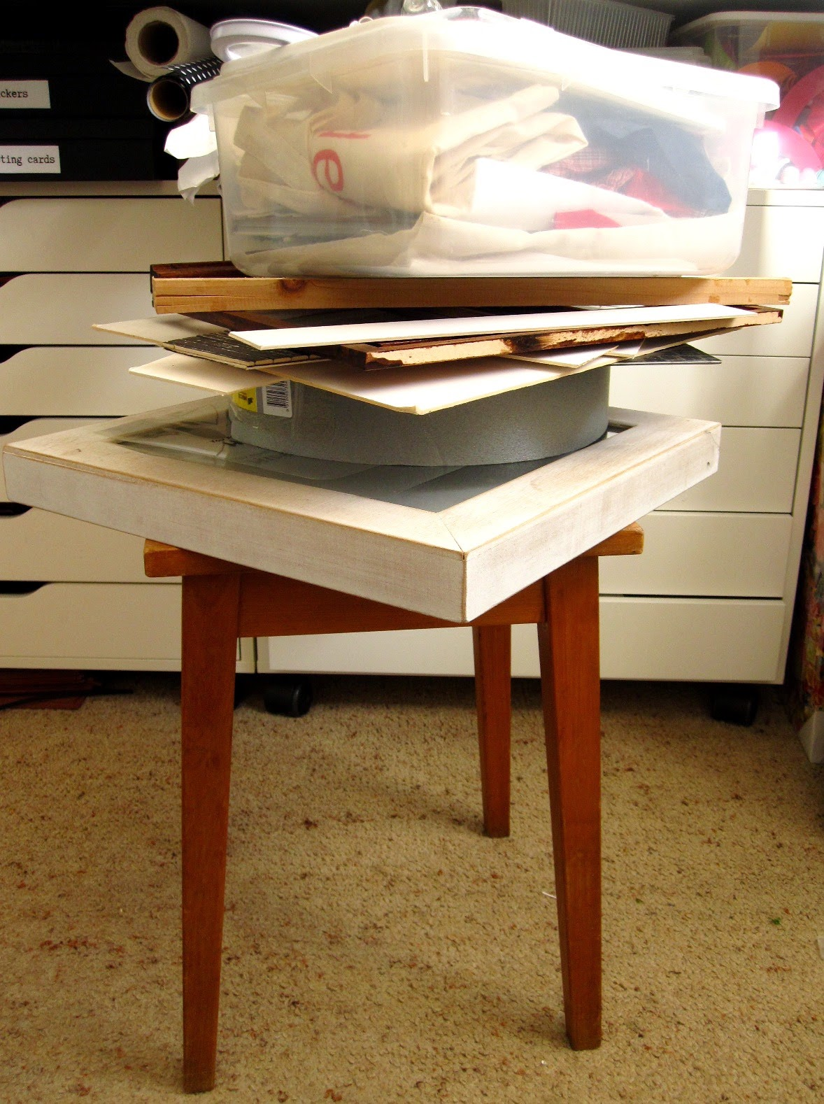 Wooden stool with a pile of wooden and cardboard pieces on top of it, topped with a plastic container full of fabric.