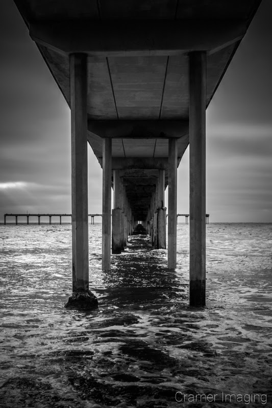 Cramer Imaging's quality black and white landscape photograph of the Pacific Ocean under the San Diego California pier