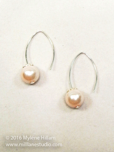 Cream pearl drops on an elfin earring wire.