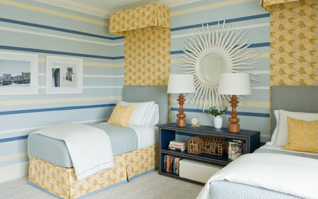 Striped walls in shades of blue and yellow coordinate with simple blue upholstered headbaords with a yellow floral crown and drape that match  the pleated bedskirts in a twin bedroom