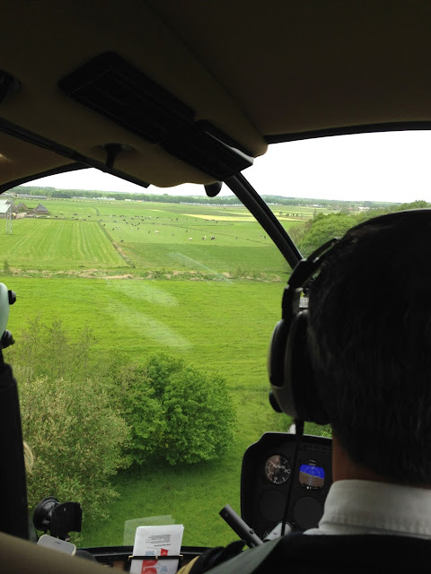 Achterkant van de piloot met zicht op landerijen door het raam van de helikopter