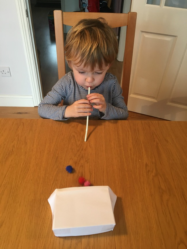 5-minute-games-for-toddlers-blow-football-image-of-toddler-with-straw-and-pompom-on-table