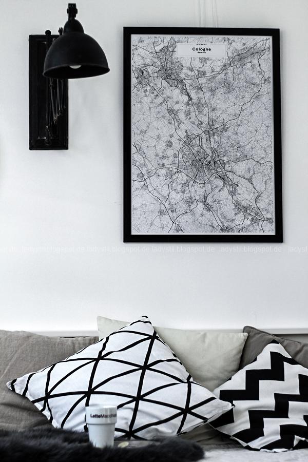 Sich die Lieblingsstadt mit einer Map nach Hause holen! Straßenkarten Landkarte im stylischen Wandbild-Format für Interiorverliebte.Schwarz-weiße Kissen auf einem Tagesbett, dahinter ein Bild von einer Köln Map