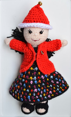 Kwokkie Doll wearing a red Christmas hat with a jingle bell on top, a red jacket over a black top and a black skirt covered in colourful polka-dots. She is wearing black sandals. She has long black hair which is tied up in a ponytail.Her button eyes are black with embroidered eye lashes. Her embroidered mouth is red.