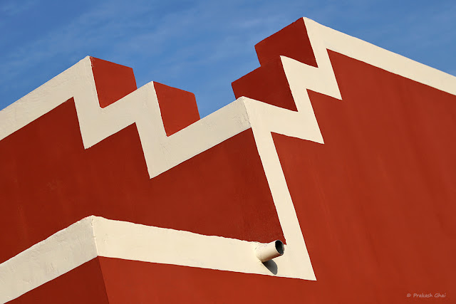A Look Up Minimal Art Image of White Lines painted on a Red Wall  with a Small Water Pipe on it.