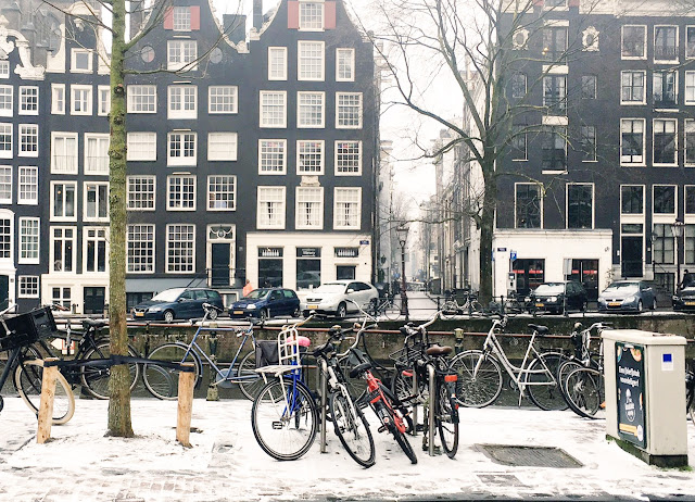 An image of a snowy Amsterdam canal and houses with bikes in the foreground