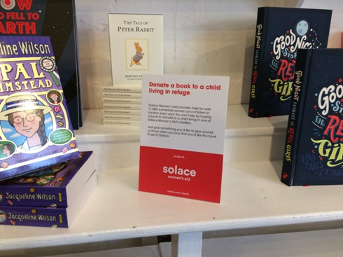 Photo of children's books, with sign about donating a book to Solace for a child