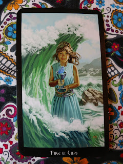 Page of Cups. Little girl holding cup with fish inside cup. She stands in ocean, wave behind her.