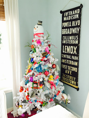 bright colored ornaments on  White Christmas tree with snowman topper