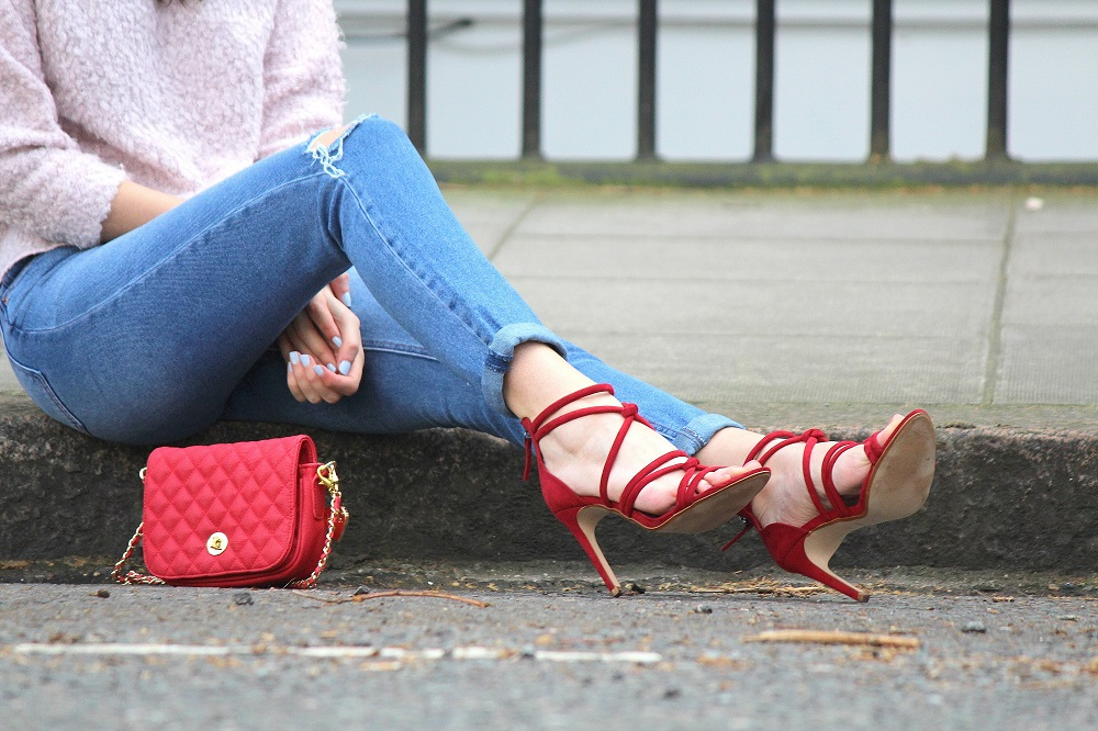 peexo fashion blogger wearing ripped mom jeans and red strappy heels and red small bag in spring
