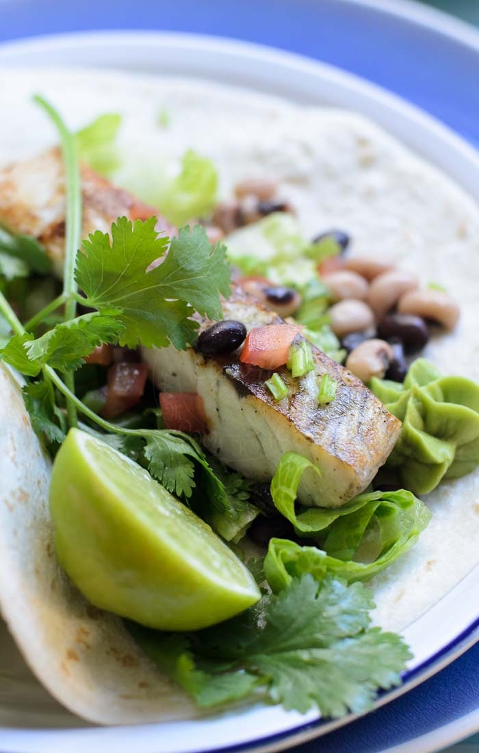Fish taco on flour tortilla with avocado puree