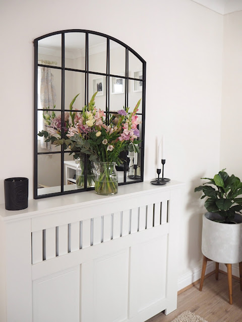 How to style a radiator cover in your living room using accessories and items you already own including artificial greenery, candles and flowers.