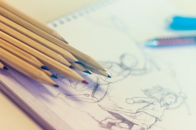 Colored pencils sitting on sketchbook, drawing, sketching