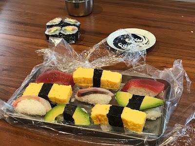Several nigiri sushi on plastic wrapping