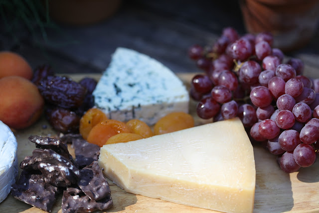 cheese board with cheese, chocolate and grapes