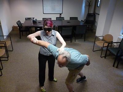 """Juodais akiniais dėvinti Polly Abbot iš organizacijos """"Second Sense"""" mokosi savigynos būdų. Jai padeda vidutinio amžiaus vyras su akiniais"""