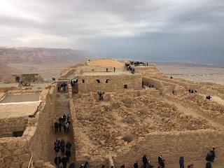 Construcciones de la antigua fortaleza de Masada llenas de gente visitándolas con el Mar Muerto de fondo