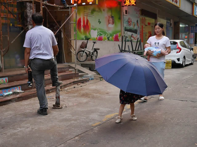a large umbrella with the legs of a kid underneath in Zhuhai, China