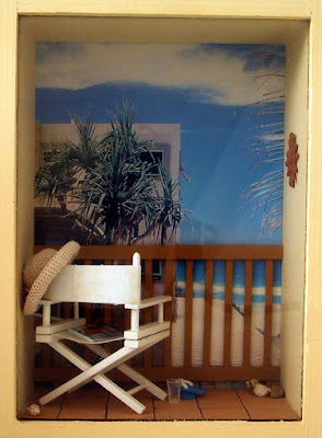 A one-twelfth scale modern miniature beach balcony scene in a box frame On balcony is a white director's chair with a woven hat on the back, a magazine on the seat, and a pair of jandals and a glass on the floor. The balcony overlooks the sea and some cabbage trees.