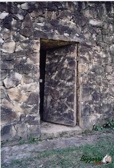 Detalhe da parede de pedra moledo com a porta de pedra moledo.