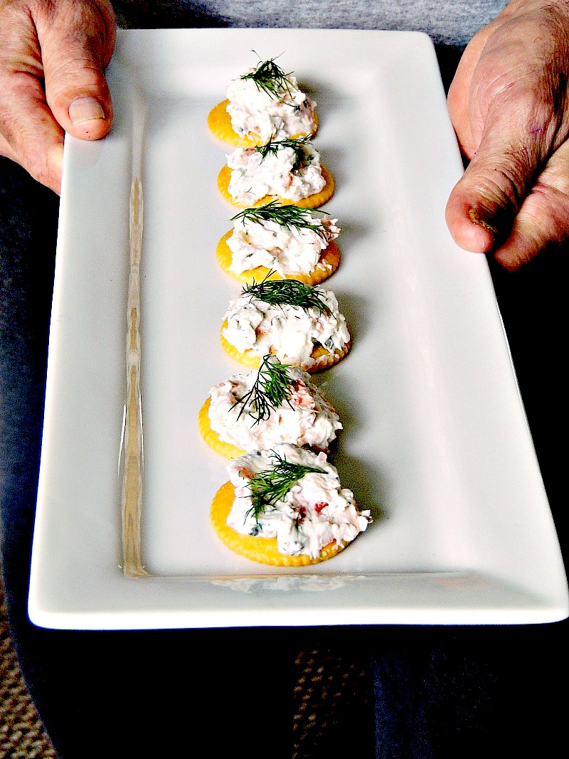 Man holding a white tray with smoked salmon appetizer bites on it.