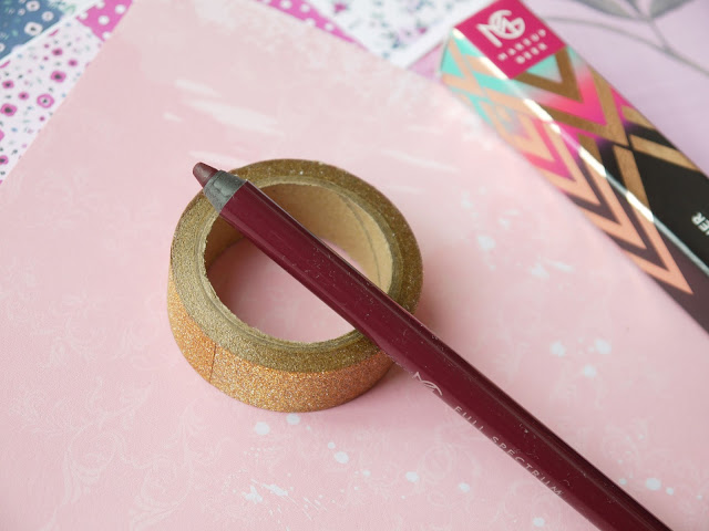 makeup geek plumeria- a black cherry coloured wooden eyeliner- on a pink background with a makeup geek box behind it