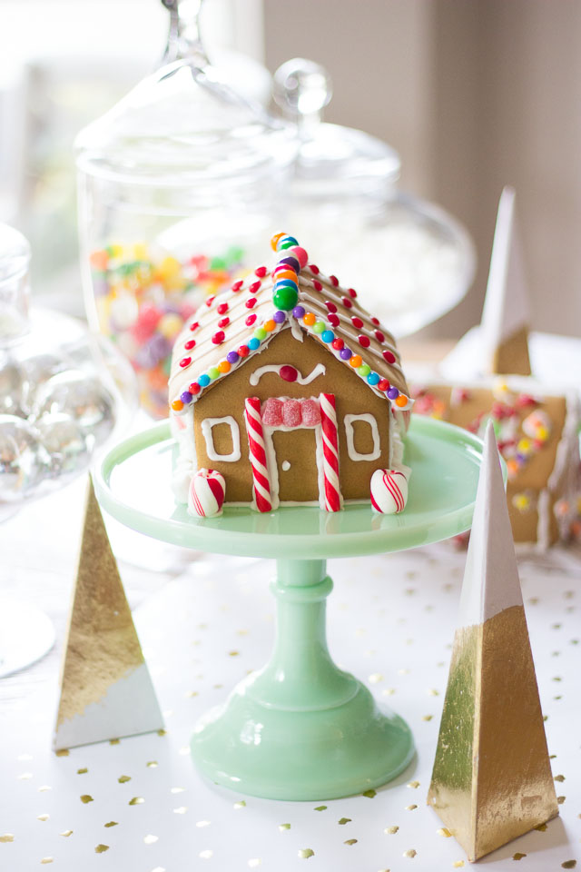 Adorable mini gingerbread house on jadeite pedestal and gold and white tablescape