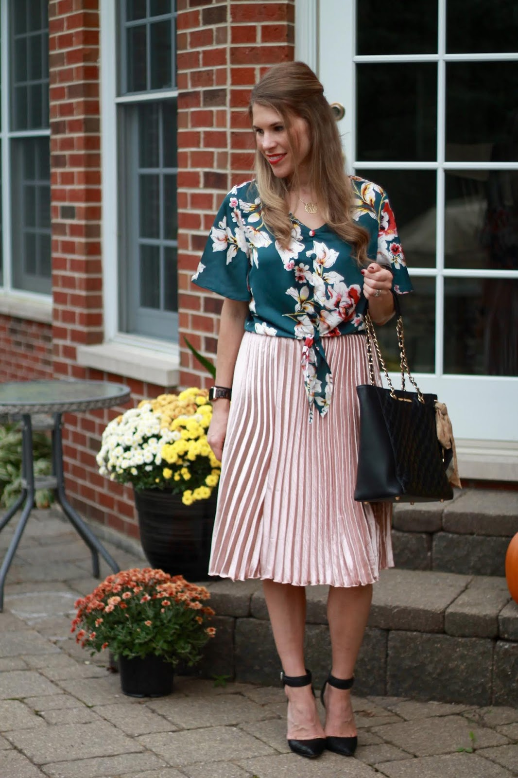 green floral tie front top, pink pleated skirt, black quilted leather tote,