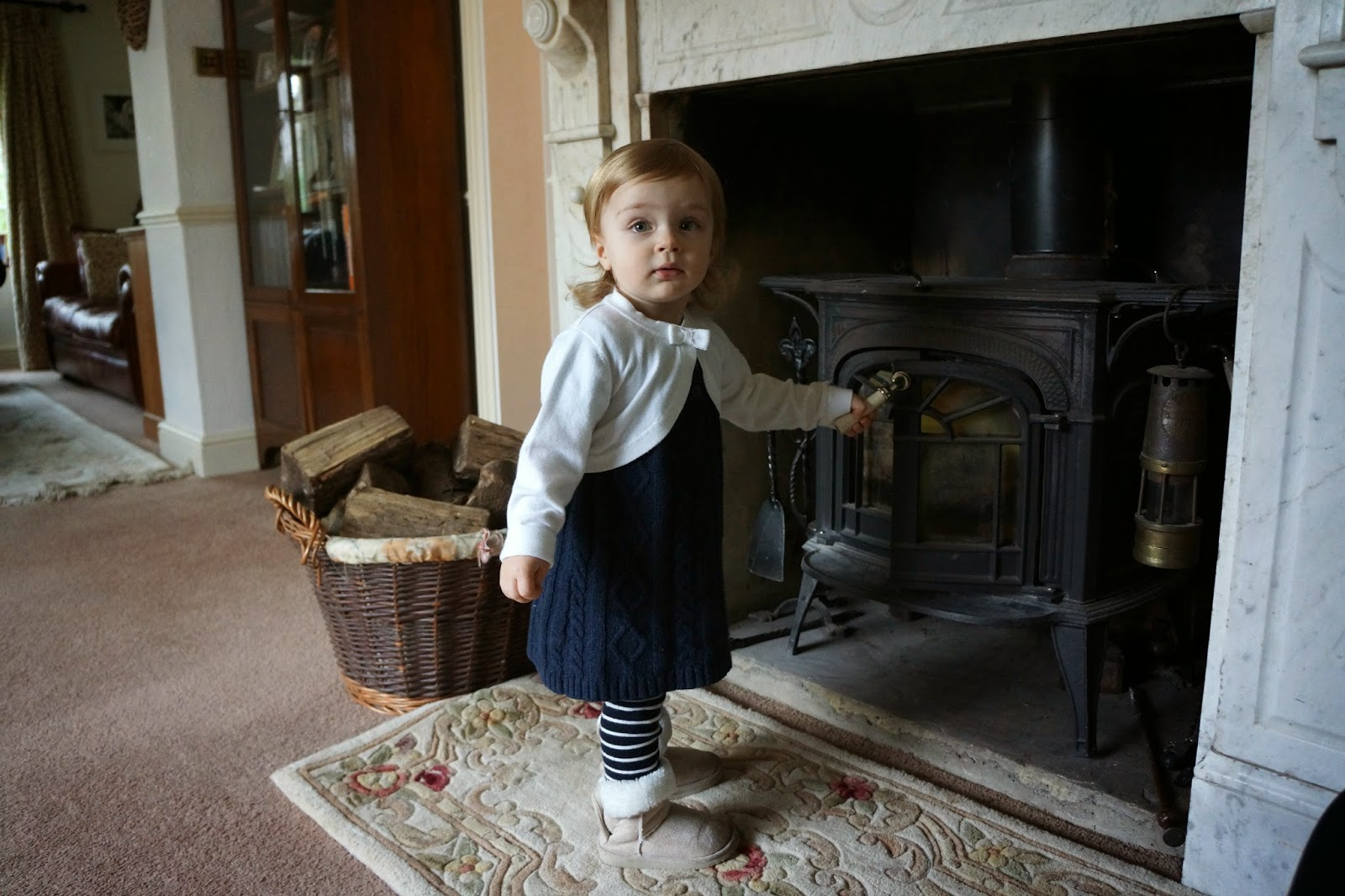 toddler standing next to a fireplace