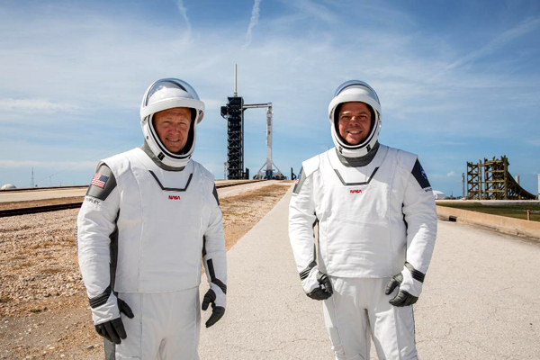 At Launch Complex (LC)-39A, NASA astronauts Doug Hurley and Bob Behnken pose in front of the Falcon 9 rocket that will send them to the International Space Station on May 27, 2020...weather permitting.