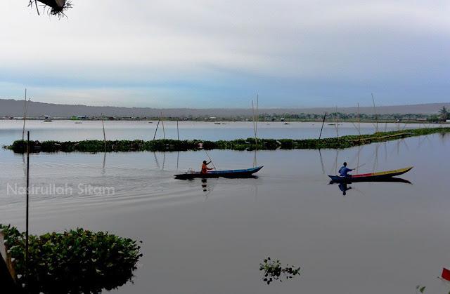 Dua sampan melaju di dekat jembatan Rawa Pening