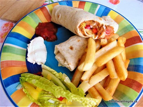 Baked Bean & Cheese Burritos on plate with sour cream, salsa, lettuce and peppers and French fries.