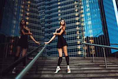 Linda chica con vestido negro parada en una escalera con edificio de fondo