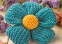http://www.letsknit.co.uk/free-knitting-patterns/quick_knit_flower_brooch