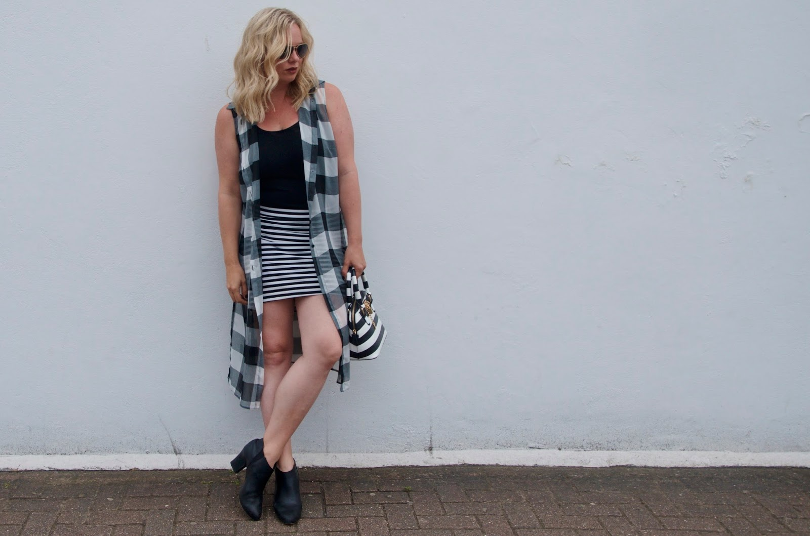 striped skirt, black booties, gingham vest, striped bag and gold aviator sunglasses