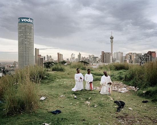 tres religiosos africanos rezando en las afueras de una ciudad con rascacielos