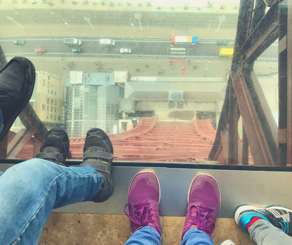 A family's feet around the glass in the floor of Blackpool Tower.