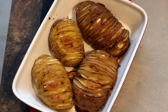 4 baked hasselback potatoes in a rectangular servicing dish.