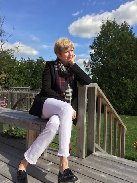 woman in white jeans, black jacket, black loafers, and scarf sitting on a deck