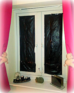 Window blacked out with black bin bags